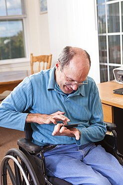 Man with Friedreich's Ataxia in wheelchair using a smartphone with deformed hands