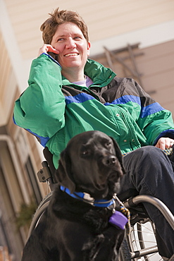 Woman with multiple sclerosis talking on a mobile phone with a service dog