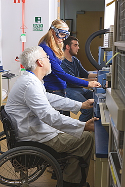 Professor with muscular dystrophy advising engineering students in chemistry laboratory working on thermogravimetric analyzers