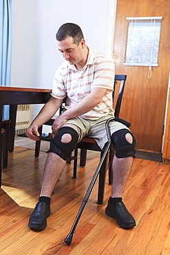 Man adjusting braces on his knees after anterior cruciate ligament (ACL) surgery