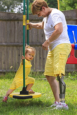 Grandmother with a prosthetic leg playing on a swing set with her granddaughter
