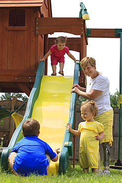 Grandmother with a prosthetic leg playing on a slide with her grandchildren