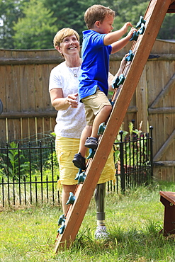 Grandmother with a prosthetic leg playing on an outdoor climber with her grandson