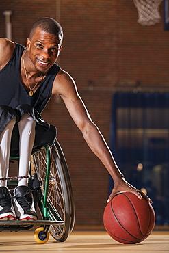 Man who had Spinal Meningitis in wheelchair picking up basketball