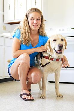 Woman with visual impairment in kitchen with her service dog