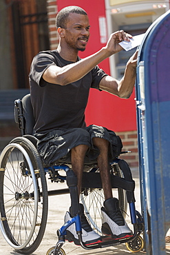 Man in a wheelchair who had Spinal Meningitis putting a letter in a public mail box