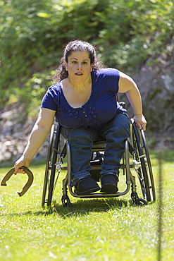 Woman with Spina Bifida in a wheelchair playing horseshoes