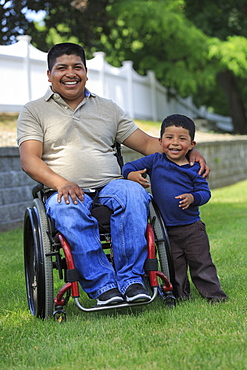 Portrait of Hispanic man with Spinal Cord Injury in wheelchair with his son in lawn