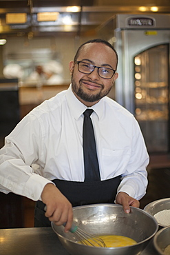 Happy African American man with Down Syndrome as a chef cooking in commercial kitchen