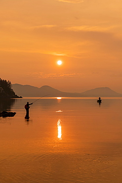Silhouetted angler standing in the tranquil water fishing for king salmon at dusk; Alaska, United States of America