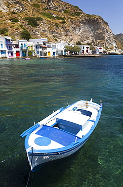 Boat moored in the water in Klima village with white houses and colourful accents along the water's edge; Klima, Milos Island, Cyclades, Greece