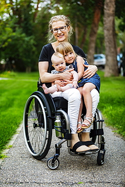 A paraplegic mom carrying her daughters on her lap while using a wheelchair outdoors on a warm summer afternoon and posing for the camera: Edmonton, Alberta, Canada