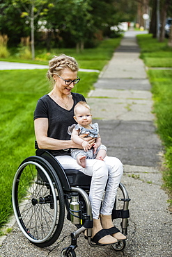 A paraplegic mom carrying her baby in her lap while using a wheelchair outdoors on a warm summer afternoon: Edmonton, Alberta, Canada