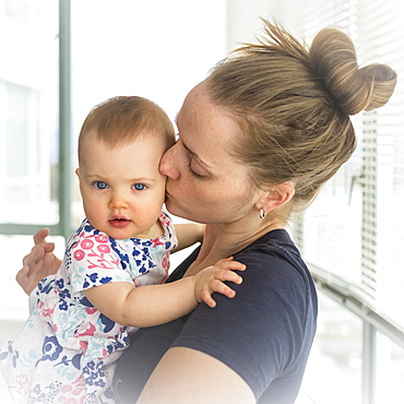 Portrait of infant baby girl with mother at home, mother kissing baby on the cheek; Vancouver, British Columbia, Canada