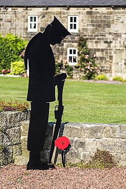 World War One memorial of a soldier with rifle and poppy; Wark, Northumberland, England