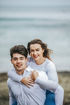 Portrait of a young couple at the beach, the young woman being carried on the young man's back; Wellington, North Island, New Zealand