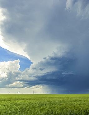 Storm cloud formations over farmland with a wind farm and turbines in the distance; United States of America