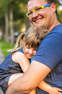 Portrait of a father cuddling with his young daughter; Edmonton, Alberta, Canada