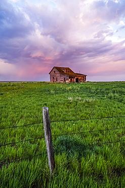 Abandoned barn on farmland with storm clouds glowing pink; Val Marie, Saskatchewan, Canada