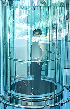Woman standing and looking out of a round glass elevator; Lugano, Ticino, Switzerland