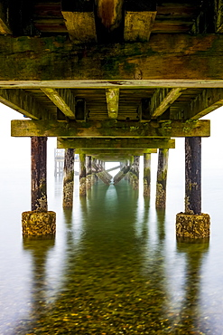 Underneath the pier on Crescent Beach on a foggy day; Surrey, British Columbia, Canada