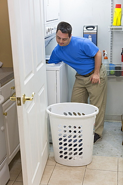 Man with Down Syndrome taking out dry clothes from washing machine