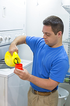 Man with Down Syndrome pouring laundry detergent
