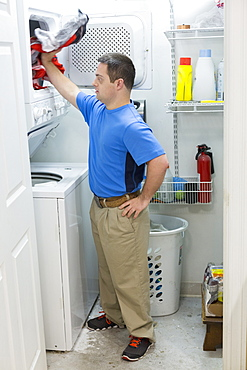 Man with Down Syndrome standing in laundry room