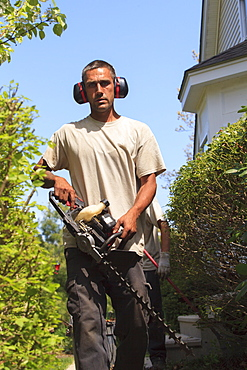 Landscaper with an electric weed trimmer and ear protectors