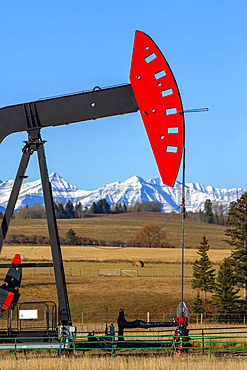 Pumpjack in a field with the foothills and snow-covered Rocky mountains in the background; Alberta, Canada