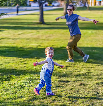A mother plays with her toddler daughter in a park; North Vancouver, British Columbia, Canada