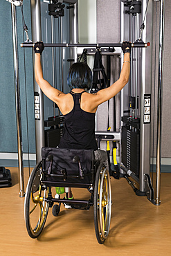 A view from behind of a paraplegic woman working out using a lat pull down machine in a fitness facility; Sherwood Park, Alberta, Canada