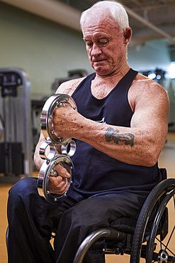 A senior paraplegic man working out using a circular handheld device in fitness facility; Sherwood Park, Alberta, Canada