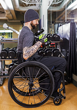 A paraplegic man working out using free weights in front of a mirror at recreational centre: Sherwood Park, Alberta, Canada