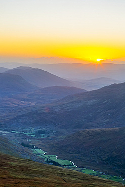 Sun rising over the Owenreagh River in the Gearsallagh Valley in MacGillycuddy's Reeks; County Kerry, Ireland