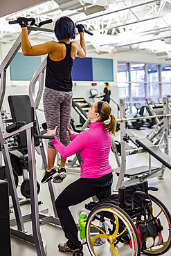 A physiotherapist assisting a paraplegic women who is doing pull-ups to increase her upper body strength, in a fitness facility: Sherwood Park, Alberta, Canada