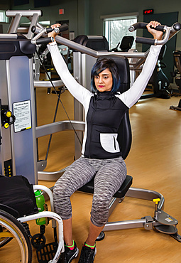 A paraplegic woman working out using an overhead press in a fitness facility; Sherwood Park, Alberta, Canada