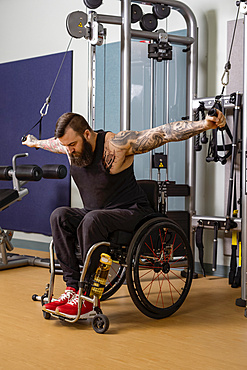 A paraplegic man working out using a crossover pulley weight lifting apparatus in a fitness facility; Sherwood Park, Alberta, Canada