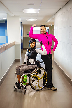 A paraplegic woman and her trainer show off their muscles while posing for the camera in a hallway in a recreational facility: Sherwood Park, Alberta, Canada