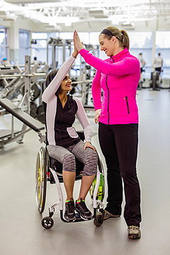 A paraplegic woman and her trainer give a high five after a successful workout in a recreational facility: Sherwood Park, Alberta, Canada