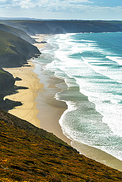 Sandy beaches with surf along a grassy cliff shoreline with blue sky and clouds; Cornwall County, England