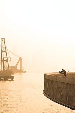 Man doing morning stretches by the Bund in Shanghai; Shanghai, Shanghai, China