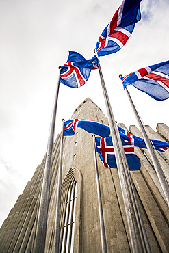 Wide angle of a grey concrete church, Hallgrimskirkja, and Icelandic flags; Reykjavik, Reykjavik, Iceland