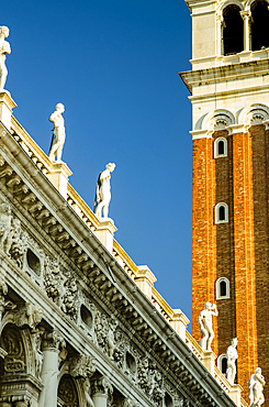 Detail of clock tower and statues along a roofline; Venice, Veneto, Italy