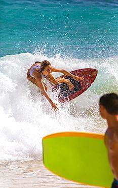 A young woman skimboarding on a wave off Sandy Beach, Oahu; Oahu, Hawaii, United States of America
