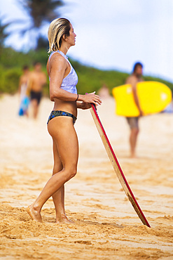 A young woman stands on Sandy Beach, Oahu, with a skimboard, looking out at the waves; Oahu, Hawaii, United States of America
