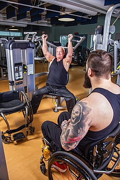 One paraplegic man working out using an overhead press in fitness facility while his disabled friend watches; Sherwood Park, Alberta, Canada
