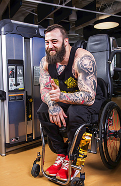 A paraplegic man looking at the camera and giving an affirming hand gesture after working out using an overhead press in a fitness facility; Sherwood Park, Alberta, Canada