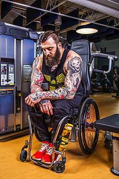 A paraplegic man resting after working out using an overhead press in fitness facility; Sherwood Park, Alberta, Canada