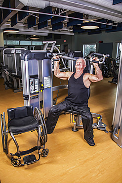 An older paraplegic man working out using an overhead press in fitness facility; Sherwood Park, Alberta, Canada
